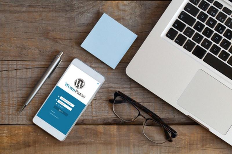 3007169-s-App-di-Wordpress-in-un-schermo-del-telefono-cellulare.-Vista-superiore-di-scrivania-in-legno-con-computer--occhiali--penna-e-post-it_800x533